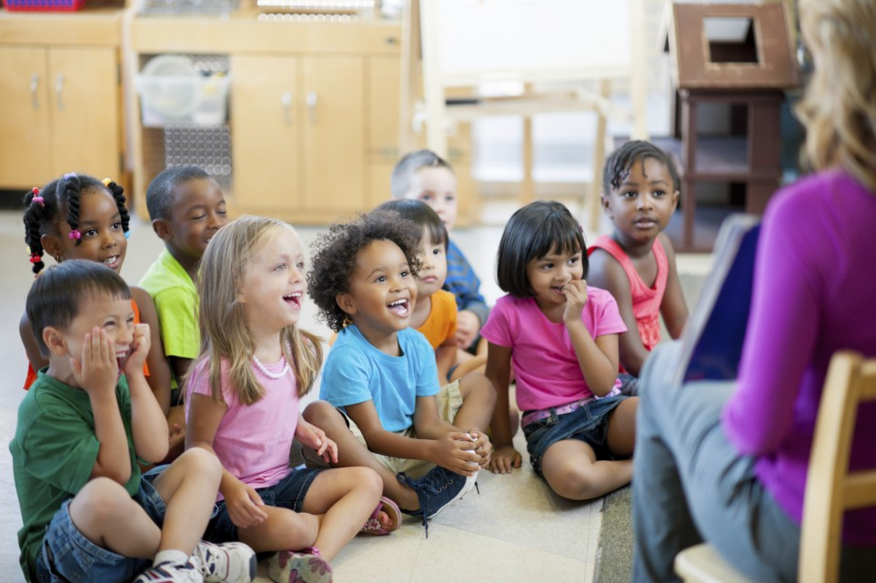 Preschoolers in circle time laughing.
