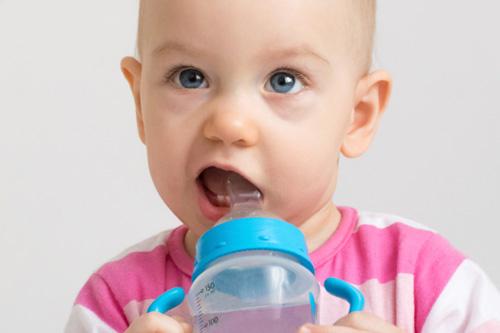 Older infant drinking from bottle.