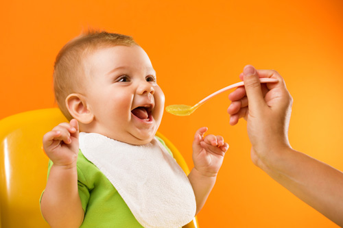 Infant opening mouth as spoon with food is approaching.