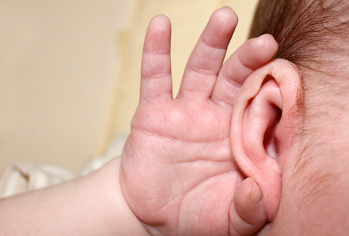 Infant hand cupping ear.