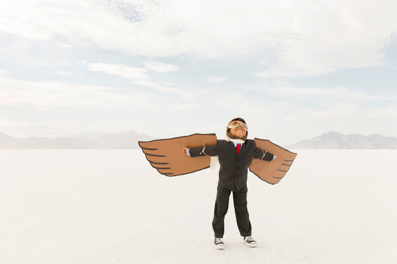 Child uses cardboard wings to pretend to fly.