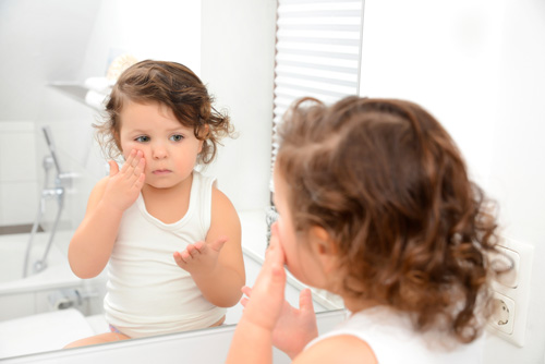 Toddler looking in mirror touching cheek.