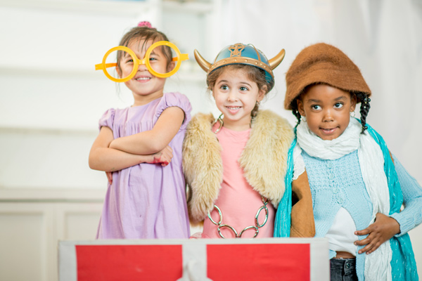 Three preschool age girls playing dress up.