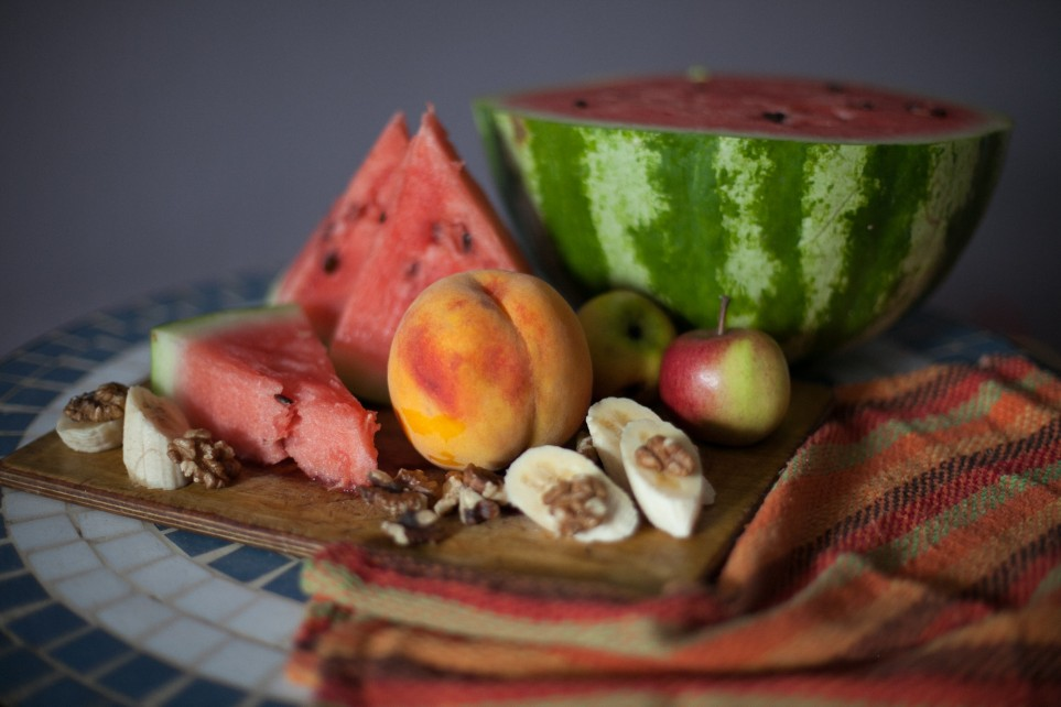 Watermelson, peaches, bannanas on a cutting board with walnuts.