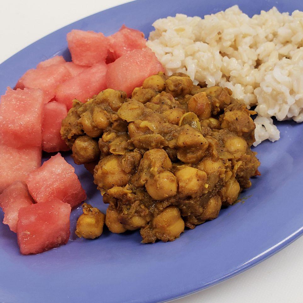 Plate with chana masala, watermelon chunks, and brown rice
